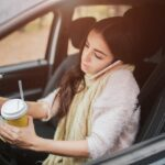 Busy woman is in a hurry, she does not have time, she is going to worck on the go. Worker is drinking hot coffee, writing in a notebook and talking on the phone at the same time. Business female person. She multitasking while using on the phone and driving a car