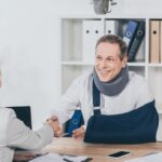 blond woman shaking hands with worker in neck brace and arm bandage over table in office, compensation concept