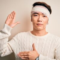 Young handsome chinese man injured for accident wearing bandage and strips on head Swearing with hand on chest and open palm, making a loyalty promise oath